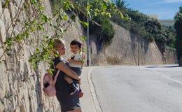 Ung moder med årig son som en och en halv går upp kullen och spelar med växter arkivbilder