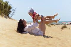 Ung moder med den lilla dottern som har gyckel på den sandiga stranden royaltyfri foto