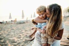Ung moder med en litet barnpojke som har gyckel på stranden på sommarferie arkivbild