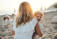 Ung moder med en litet barnpojke som har gyckel p? stranden p? sommarferie arkivbild