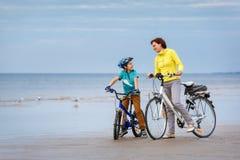 Ung moder med hennes lilla son som rider cyklar på stranden royaltyfri bild