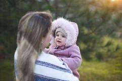 Ung moder och att behandla som ett barn dottern utanför tillsammans Autumn Portrait royaltyfri bild
