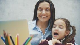 Ung moder och dotter som sitter på tabellen på en grå bakgrund Under detta håller ögonen på en grå bärbar dator arkivfilmer
