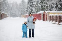 Ung moder och henne dotter i snowfall arkivbild