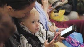 Ung moder och liten son som använder telefonen medan lopp med gångtunneldrevet lager videofilmer