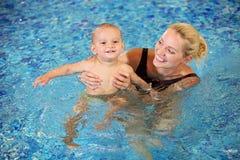 Ung moder och liten son som har gyckel i en swimmi Royaltyfri Foto