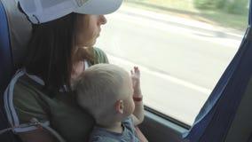 Ung moder och liten sonritt på en buss under solig dag Lopp turism, familjbegrepp lager videofilmer