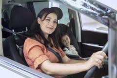 Ung moder som kör en bil med hennes dotter fotografering för bildbyråer