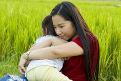 Ung moder som kramar och lugnar en skriande liten dotter, en asiatisk moder som f?rs?ker att tr?sta och lugna ner hennes skriande arkivbild