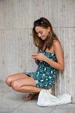 Ung moderiktig flicka (21) som bläddrar internet med hennes mobiltelefon Royaltyfri Foto