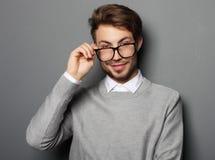 Ung moderiktig man med exponeringsglas som ler, studioskott royaltyfria bilder