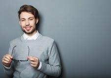 Ung moderiktig man med exponeringsglas som ler, studioskott royaltyfri fotografi