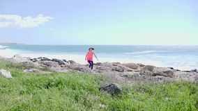Ung motiverad sportive kvinna som kör på en slinga in mot kameran Starkt stormigt hav på bakgrunden l?ngsam r?relse stock video