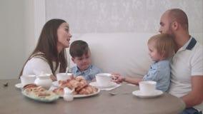 Ung mum och farsa som har gyckel med två lilla söner på tetabellen arkivfilmer