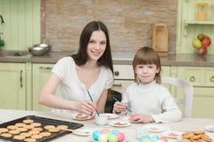 Ung mum och hennes liten son som tillsammans bakar och dekorerar muffierna fotografering för bildbyråer