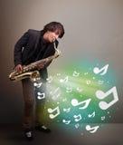 Ung musiker som spelar på saxofonen medan explodin för musikaliska anmärkningar Royaltyfri Bild