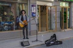 Ung musikerpojke som spelar gitarren och sjungande sånger på gatan Arkivfoto