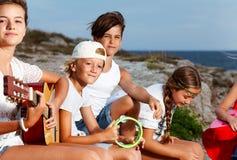 Ung musikmusikband som spelar akustiska gitarrer utomhus fotografering för bildbyråer