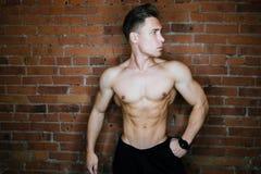 Ung muskulös kroppsbyggarekonditionmodell som poserar mot en klubba för kondition för vind för tegelstenvägg Skönhetcirkelexponer Royaltyfri Foto