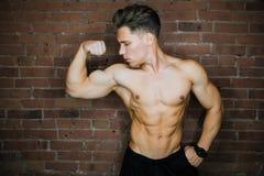 Ung muskulös kroppsbyggarekonditionmodell som poserar mot en klubba för kondition för vind för tegelstenvägg Skönhetcirkelexponer Royaltyfri Bild