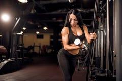 Ung muskulös kvinna som gör genomkörare på idrottshallen royaltyfri bild