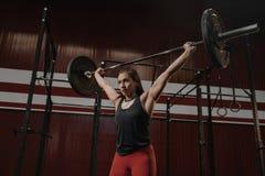 Ung muskulös kvinna som gör tyngdlyftningövningar på crossfitidrottshallen royaltyfria bilder