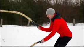 Ung muskulös man i röd omslagsutbildning med stridrepvinter och snöultrarapid Konditiongenomkörare utomhus arkivfilmer