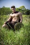 Ung muskulös man som poserar i gladiatordräkt Arkivfoto