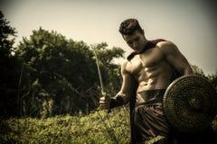 Ung muskulös man som poserar i gladiatordräkt Arkivbilder