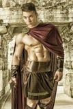Ung muskulös man som poserar i gladiatordräkt Royaltyfri Fotografi