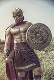 Ung muskulös man som poserar i gladiatordräkt Royaltyfri Bild