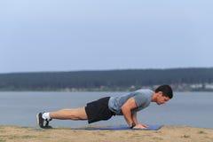 Ung muskulös man som utomhus gör push-UPS Royaltyfri Foto