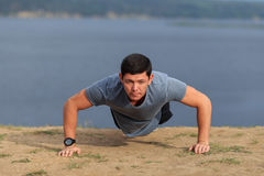 Ung muskulös man som utomhus gör push-UPS Fotografering för Bildbyråer