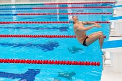 Ung muskulös simmarebanhoppning från det startande kvarteret i en simbassäng Royaltyfria Foton