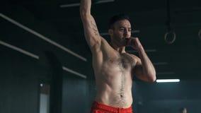 Ung muskul?s man som g?r ?vningar med kettlebell i idrottshall Tyngdlyftninggenomk?rare Sportar konditionbegrepp 4K saktar arkivfilmer