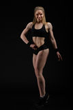 Ung muskulös kvinna som poserar på svart Arkivbilder