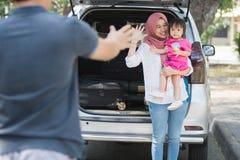 Ung muslim familj, transport, fritid, vägtur och folkbegrepp - lycklig kvinna och liten flicka som vinkar på fadern för att säga royaltyfri foto