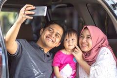 Ung muslim familj, transport, fritid, vägtur och folkbegrepp - slut upp man, kvinna och liten flicka för stående lycklig royaltyfria bilder