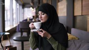 Ung muslim kvinna som bär svart hijab som sitter i modernt kafé Dricka kaffe från den vita koppen och hänsynsfullt lager videofilmer