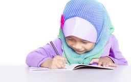 Ung muslimflicka som skriver en bok på skrivbordet arkivbild