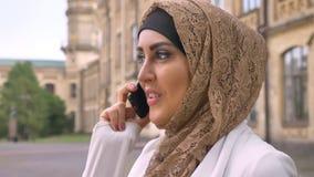 Ung muslimkvinna i hijab som talar på telefonen och anseende på gatan, byggnad i bakgrund, affärsdam i vit stock video