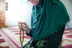 Ung muslimkvinna som ber i mosk?n royaltyfria bilder