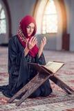 Ung muslimkvinna som ber med radbandet i moské arkivbilder