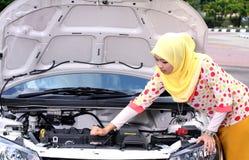 Ung muslimkvinna som kontrollerar motorn Arkivfoto