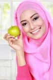 Ung muslimkvinna som rymmer ett äpple Arkivbild