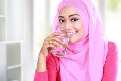 Ung muslimkvinnadrink per exponeringsglas av vatten arkivbilder