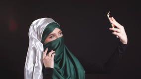 Ung muslimsk flicka i Hijab som gör Selfie på mobiltelefonkamera stock video