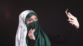 Ung muslimsk flicka i Hijab som gör Selfie på mobiltelefonkamera lager videofilmer