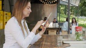 Ung nätt affärskvinna som använder minnestavlaPC på lunchavbrott i ett utomhus- kafé lager videofilmer