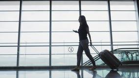 Ung nätt affärskvinna Using en Smartphone på flygplatsen, medan vänta hennes kö för registreringen, resande begrepp Arkivfoton